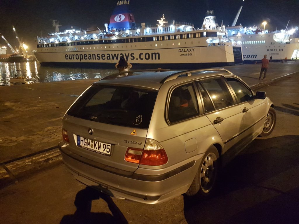 Car in front of a ship
